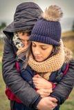 Giovani coppie con il cappello e la sciarpa che abbracciano all'aperto Fotografia Stock Libera da Diritti