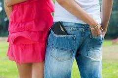 Giovani coppie con il cellulare nella tasca Fotografia Stock
