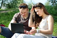 Giovani coppie con il computer portatile Fotografia Stock Libera da Diritti