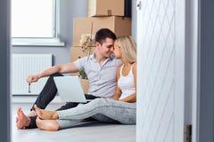 Giovani coppie con il computer portatile sul pavimento in una nuova casa fotografie stock