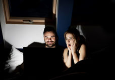 Giovani coppie con il film di sorveglianza del computer portatile a letto Immagini Stock Libere da Diritti