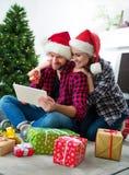 Giovani coppie con il GIF online di compera di Natale dei cappelli di Santa Claus Fotografie Stock Libere da Diritti