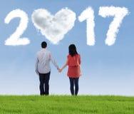 Giovani coppie con il numero a forma di 2017 della nuvola Fotografie Stock