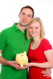 Giovani coppie con il porcellino salvadanaio fotografia stock libera da diritti
