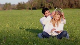 Giovani coppie con la compressa che digitale una testa telefona stock footage