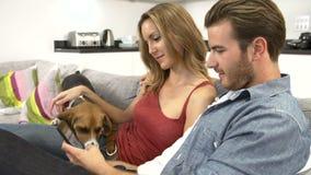 Giovani coppie con la compressa di Sit On Sofa Using Digital del cane stock footage