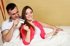 Giovani coppie con la compressa e la carta di credito a casa Immagine Stock Libera da Diritti