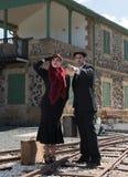 Giovani coppie con la valigia d'annata sui trainlines pronti per la a Fotografia Stock