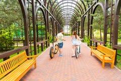 Giovani coppie con le bici in arco Fotografia Stock