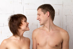 Giovani coppie con le emozioni allegre vicino alla parete bianca Fotografie Stock