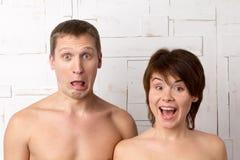 Giovani coppie con le emozioni della sorpresa vicino alla parete bianca Immagine Stock