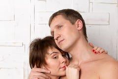 Giovani coppie con le emozioni di dreaminess vicino alla parete bianca Fotografia Stock Libera da Diritti