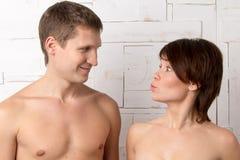 Giovani coppie con le emozioni di repentinità vicino alla parete bianca Fotografia Stock