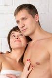 Giovani coppie con le emozioni di tenerezza vicino alla parete bianca Immagine Stock