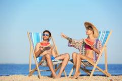 Giovani coppie con le fette dell'anguria nelle sedie di spiaggia immagine stock