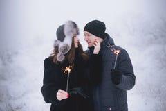 Giovani coppie con le stelle filante nella famiglia sorridente della foresta di inverno con le luci di Bengala Fotografie Stock