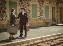 Giovani coppie con le valigie d'annata sulla stazione ferroviaria Fotografia Stock Libera da Diritti