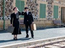 Giovani coppie con le valigie d'annata sulla stazione ferroviaria Immagine Stock