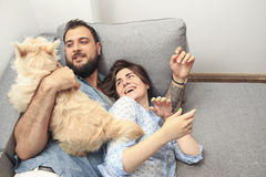 Giovani coppie con un cane a casa Fotografie Stock