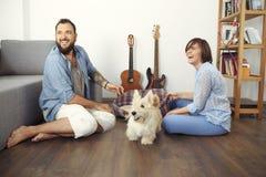 Giovani coppie con un cane a casa Fotografia Stock