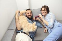 Giovani coppie con un cane a casa Immagine Stock