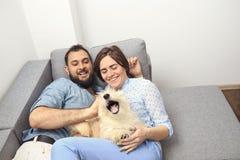 Giovani coppie con un cane a casa Fotografie Stock Libere da Diritti