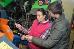 Giovani coppie d'agricoltura allegre che controllano il loro trattore prima del raccolto Immagini Stock