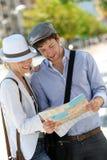 Giovani coppie d'avanguardia che esaminano la città facente un giro turistico della mappa Fotografie Stock