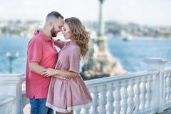 Giovani coppie degli amanti ad inizio della storia di amore - l'uomo bello di modo bisbiglia i baci sexy in orecchio grazioso del Immagine Stock Libera da Diritti