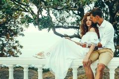 Giovani coppie degli amanti che si siedono su una balaustra, uomo che abbraccia una donna Rilassi insieme il concetto di stile di Immagine Stock
