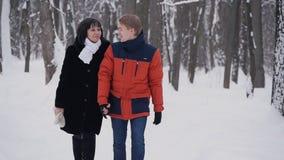 Giovani coppie dei pantaloni a vita bassa che hanno una passeggiata nella foresta di inverno al rallentatore archivi video
