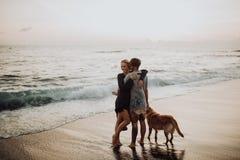 Giovani coppie dei pantaloni a vita bassa di bella risata felice con il golden retriever sulla spiaggia oceano una sabbia Onde co immagini stock libere da diritti