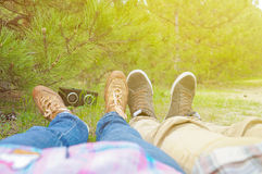 Giovani coppie dei pantaloni a vita bassa nell'amore che si trova sull'erba e sulla musica d'ascolto nel parco verde del sammer V Fotografia Stock