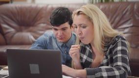Giovani coppie del ritratto che si siedono davanti ad un taccuino a casa Uomo castana bello e donna bionda sveglia che lavorano a archivi video