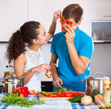 Giovani coppie della famiglia che cucinano le verdure Immagine Stock Libera da Diritti