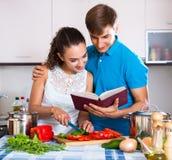 Giovani coppie della famiglia che cucinano le verdure Fotografia Stock Libera da Diritti