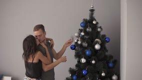 Giovani coppie della moglie e del marito che preparano per il nuovo anno o il Natale Abbracciando condizione vicino all'albero di archivi video