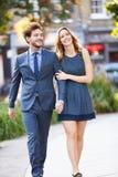 Giovani coppie di affari che camminano insieme attraverso il parco della città Fotografia Stock