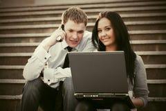 Giovani coppie di affari con il computer portatile sui punti Fotografie Stock Libere da Diritti