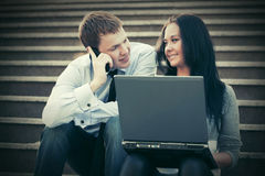 Giovani coppie di affari con il computer portatile sui punti Immagini Stock