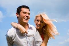 Giovani coppie di amore che sorridono sotto il cielo blu Fotografia Stock Libera da Diritti