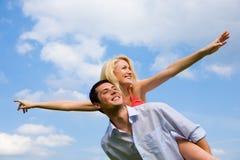 Giovani coppie di amore che sorridono sotto il cielo blu Immagine Stock