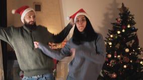 Giovani coppie di divertimento in cappelli di Santa che ballano e che saltano nella stanza davanti all'albero di Natale L'uomo e  video d archivio