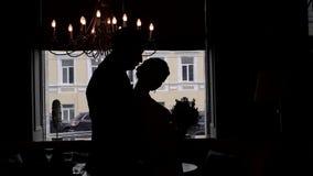 Giovani coppie di nozze che ballano contro una finestra in siluetta stock footage