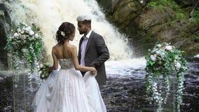 Giovani coppie di nozze che camminano alla cerimonia vicino alla cascata stock footage
