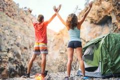 Giovani coppie di salute che fanno yoga accanto al fuoco mentre accampandosi con la tenda su una montagna - amici che meditano in immagini stock libere da diritti