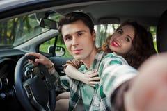 Giovani coppie divertendosi dentro un'automobile e facendo selfie Fotografia Stock Libera da Diritti
