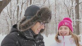 Giovani coppie divertendosi insieme nella neve nelle palle di neve di lancio del terreno boscoso di inverno archivi video