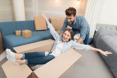 Giovani coppie divertendosi mentre muovendosi verso il nuovo appartamento Persone appena sposate commoventi La ragazza sta sedend Fotografia Stock Libera da Diritti