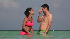 Giovani coppie divertendosi nuoto stock footage